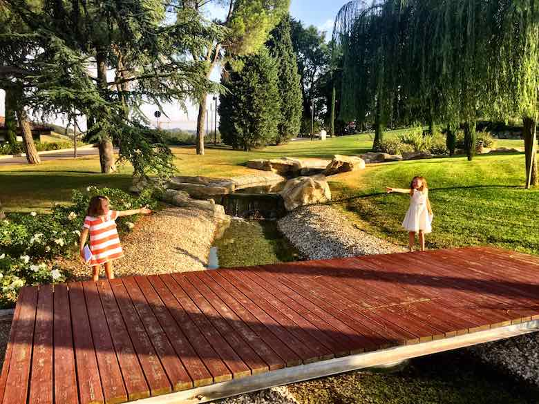 Two sisters in dresses reaching out from both sides of a wooden bridge at the meticulously manicured park of Palazzo di Varignana Resort & Spa near Bologna
