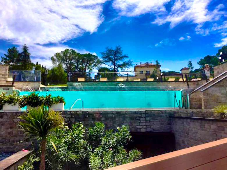 The transparant pool with in the backdrop the palazzo at the domain of Palazzo di Varignana Resort & Spa near Bologna