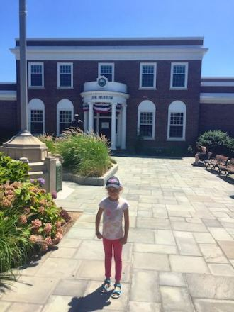 Little girl standing in front of the JFK museum in Hyannis, Cape Cod