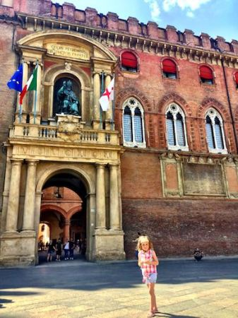A girl posing in front of the facade of Palazzo d'Accursio, housing City Art Collection and Town Hall in Bologna