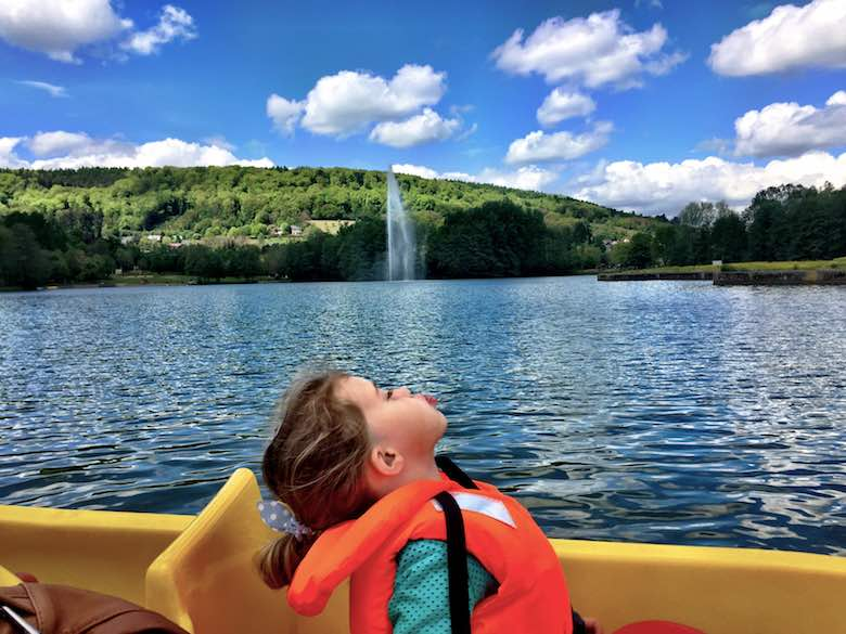 CosmopoliKid Jade on a pedalo boat acting as if the fountain of Lake Echternach is coming from her mouth