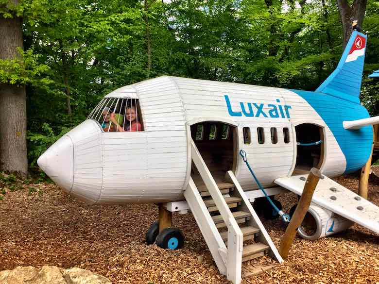 CosmopoliKids Alegra & Jade waving from a Luxair play plane in Parc Merveilleux during a family trip to Luxemburg with kids