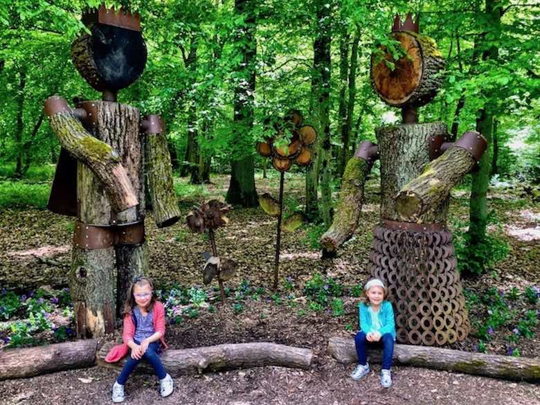 Two girls posing with two giant wooden statues of a queen and king in Parc Merveilleux in Luxemburg