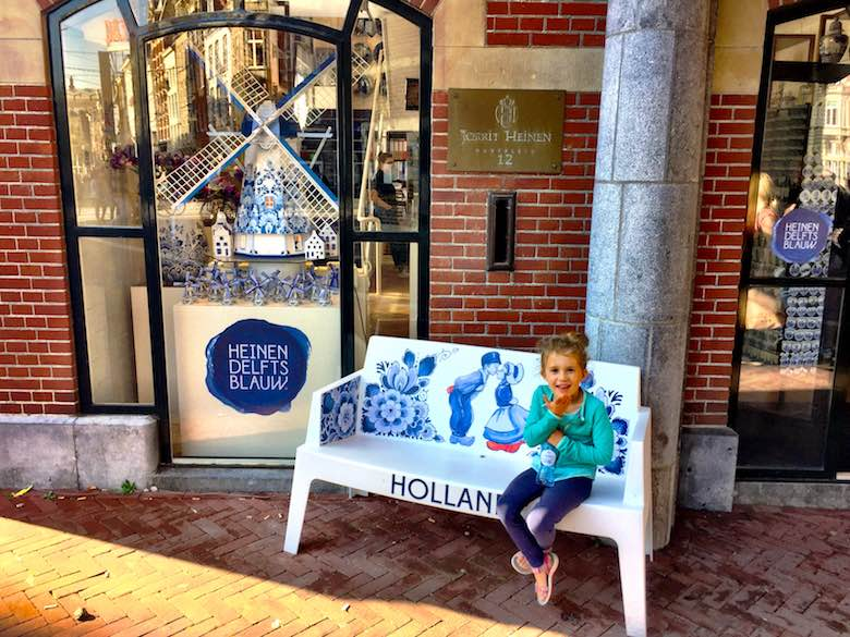 Happy little girl throwing a kiss to the camera from a Delftware themed bench in front of the Royal Delfware shop in Amsterdam