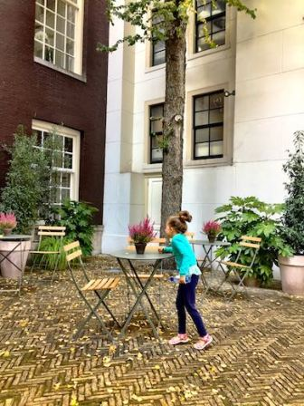 Little Jade smelling the flowers in The Dylan hotel in the Negen Straatjes district during a mother-daughter trip to Amsterdam