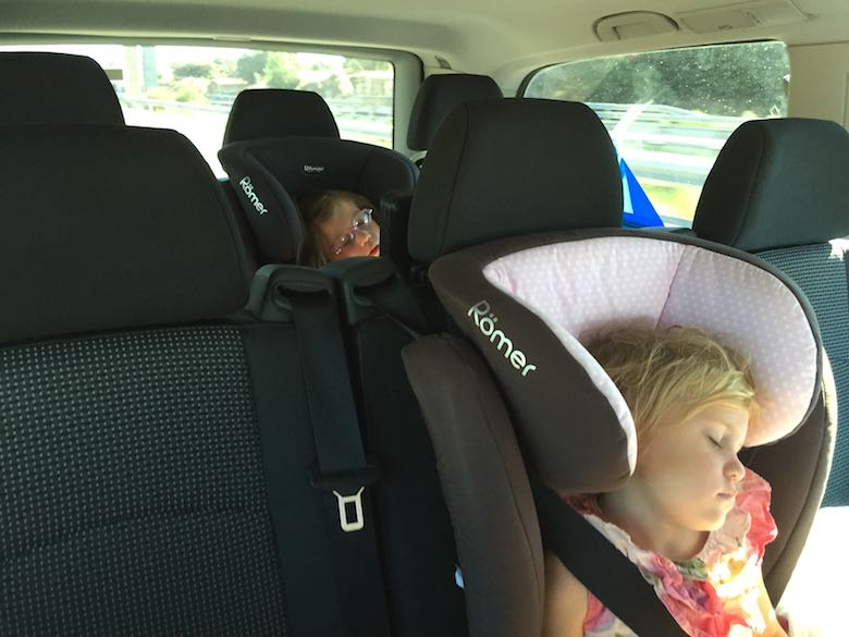 Two sisters sleeping in their car seat, each on a separate seating row of a minivan