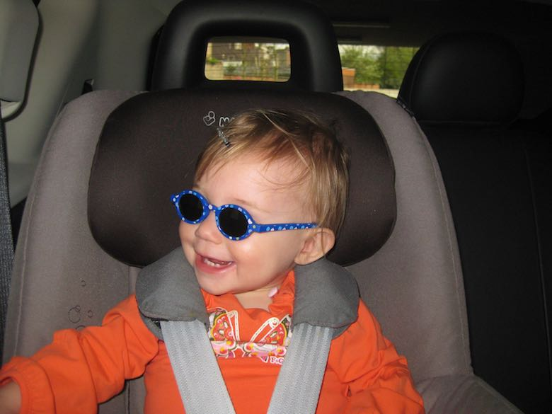 Little girl wearing sunglasses and smiling in het car seat