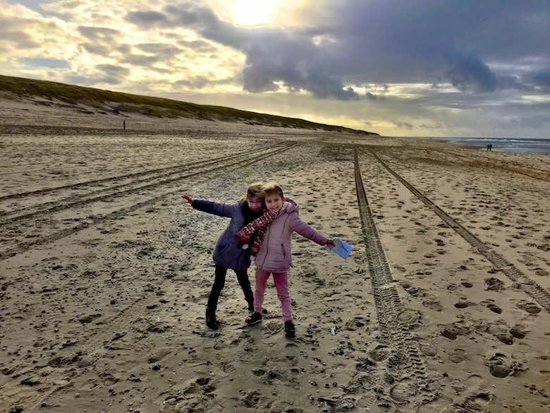 Twee zusjes in winterjas poseren op het brede zandstrand van Texel