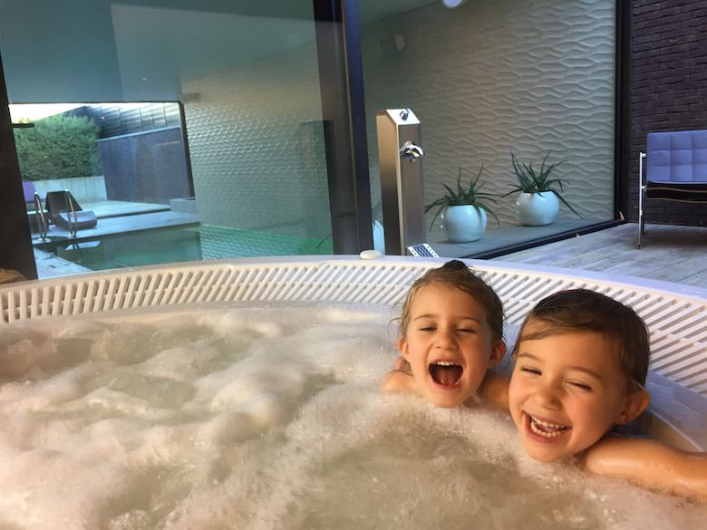 Two sisters laughing and having fun in the outdoor jacuzzi