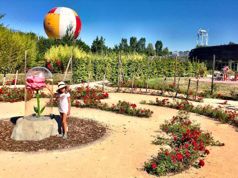 Little girl wearing a hat touching the Rose at the Parc du Petit Prince, de tussenstop die je niet mag missen tijdens een autovakantie met kinderen naar Italië
