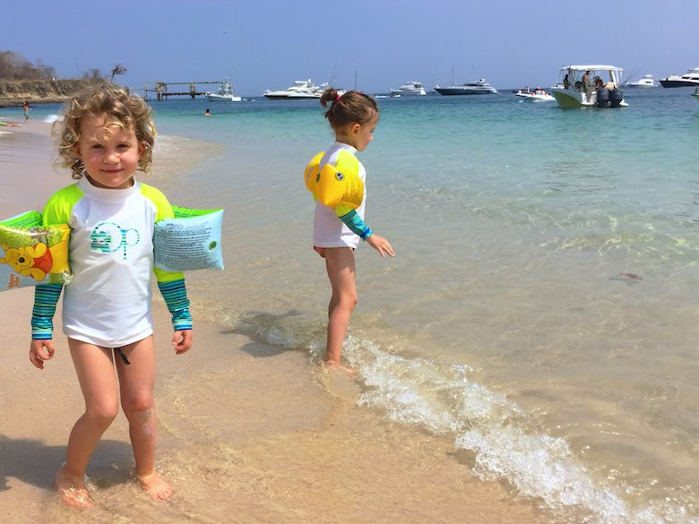 Two sisters enjoying the surf at the beach of Isla Contadora, the ultimate one-day beach getaway from Panama City