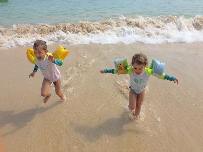 Two sisters running from the waves at Isla Contadora, the ultimate one-day beach getaway from Panama City