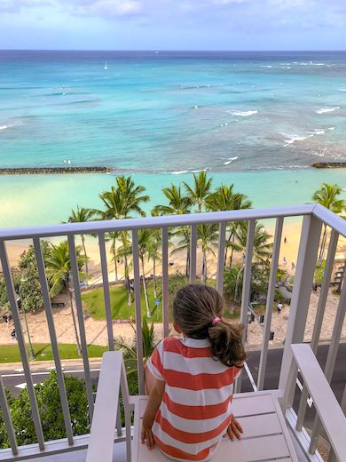 Little girl overlooking Waikiki Beach from the private lanai of a Premier Ocean Front room in the Beachside tower of the Alohilani Resort in Waikiki Beach