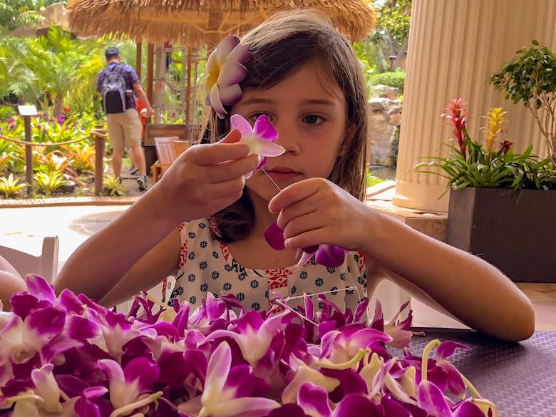 Girl making a fresh flower lei, one of the things to do in Maui with kids