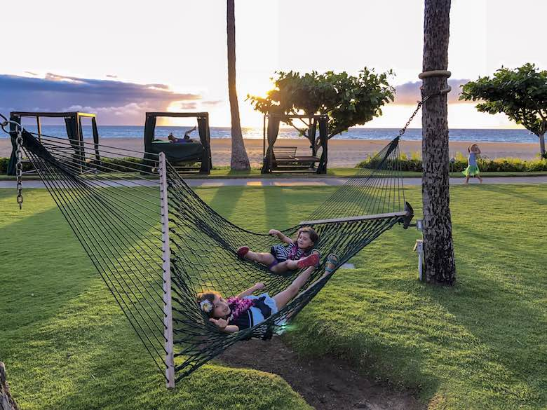 Two girls relaxing in a hammock during sunset, the perfect ending of a Maui day trip