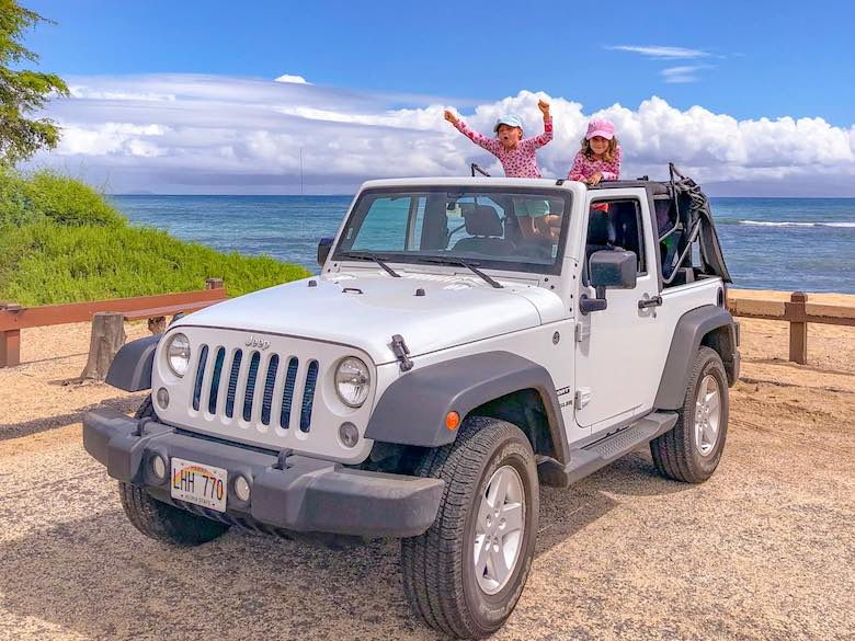 Two little girls cheering while standing up in a jeep wrangler