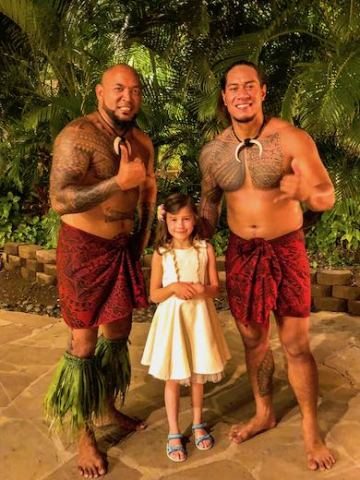 Little girl in a white dress posing with the Polynesian dancers after their performance at the Maui luau in the Westin Kaanapali