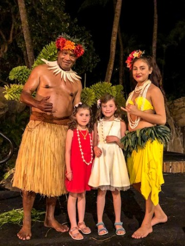Two little girls posing with the Fijian dancers after their performance at the Wailele Polynesian Luau