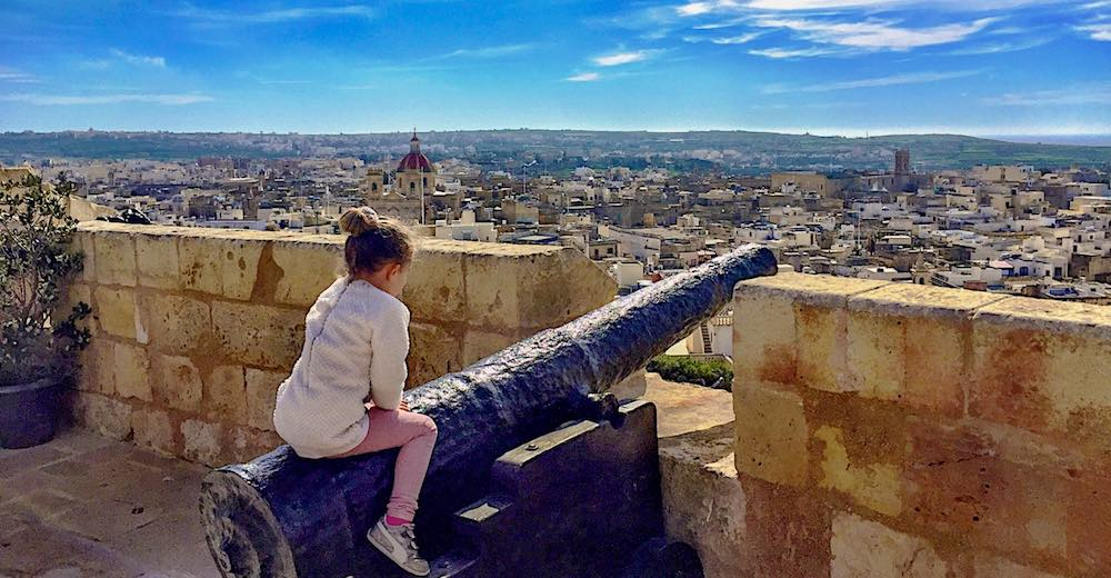 Little girl sitting on a canon while taking in the gorgeous views from the Ciutadella in Victoria, Gozo