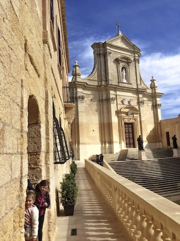Two girls hiding in a portico of Gozo's Ciutadella
