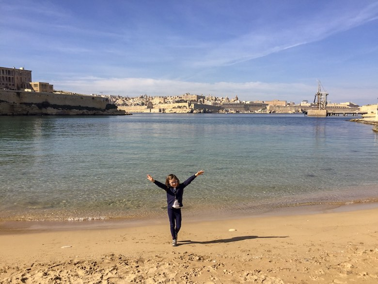 Little girl with hands in the air at Rinella Bay, a tiny beach in Three Cities Malta
