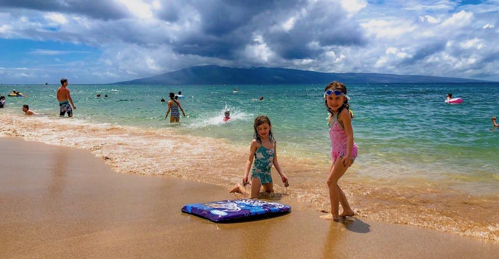 Two girls playing on the beach of Ka'anapali, one of the best places to stay in Maui