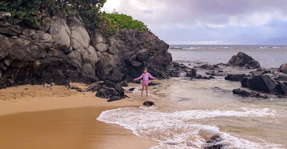 Little girl standing in the rain in Kapalua which is the rainiest place in West Maui, consider that when looking where to stay in Maui