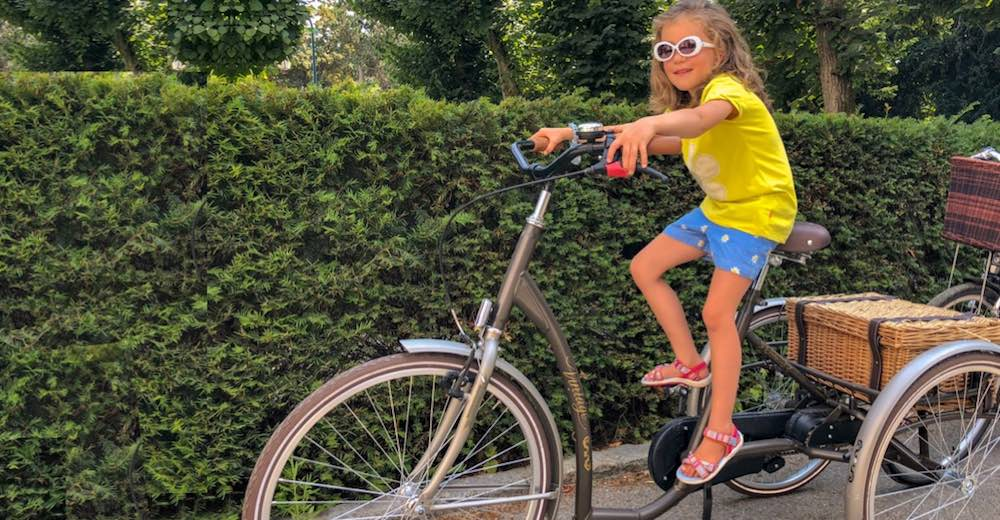Little girl in a yellow t-shirt on one of the picnic bikes of the Waldorf Astoria Trianon Palace Versailles