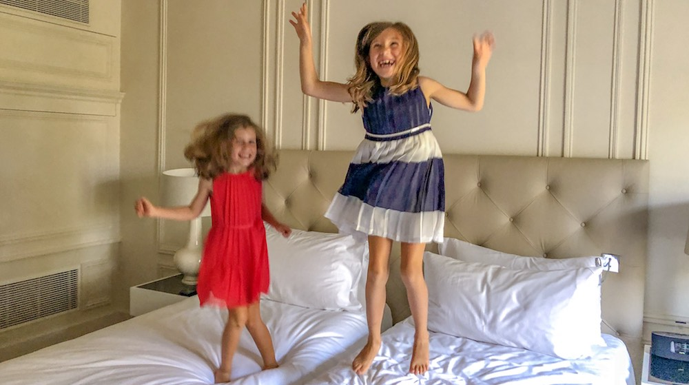 Two little girls jumping on the bed in a Deluxe Palace Family Room with garden view at the Trianon Palace Versailles, a Waldorf Astoria hotel
