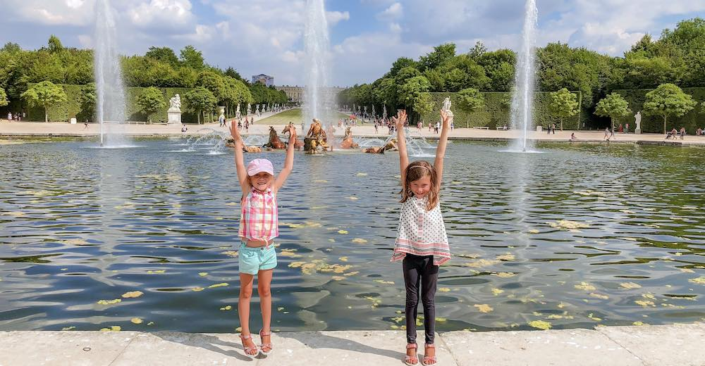 Two little girls raising their arms to draw attention to the Musical Fountains show in the Gardens of Versailles