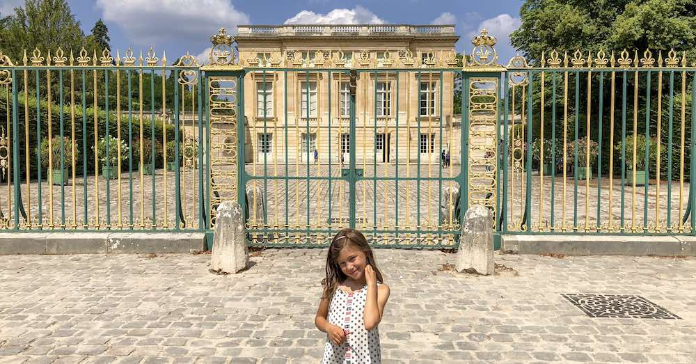 Little girl posing in front of the Petit Trianon, Marie Antoinette's estate in Versailles France
