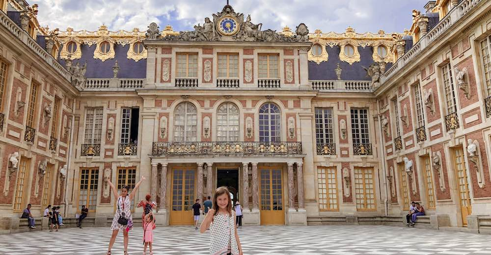 Little girl at the Marble Courtyard while visiting the Versailles Palace