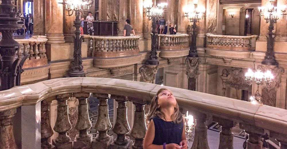 Little girl admiring the ceiling of the Palais Garnier while visiting Paris