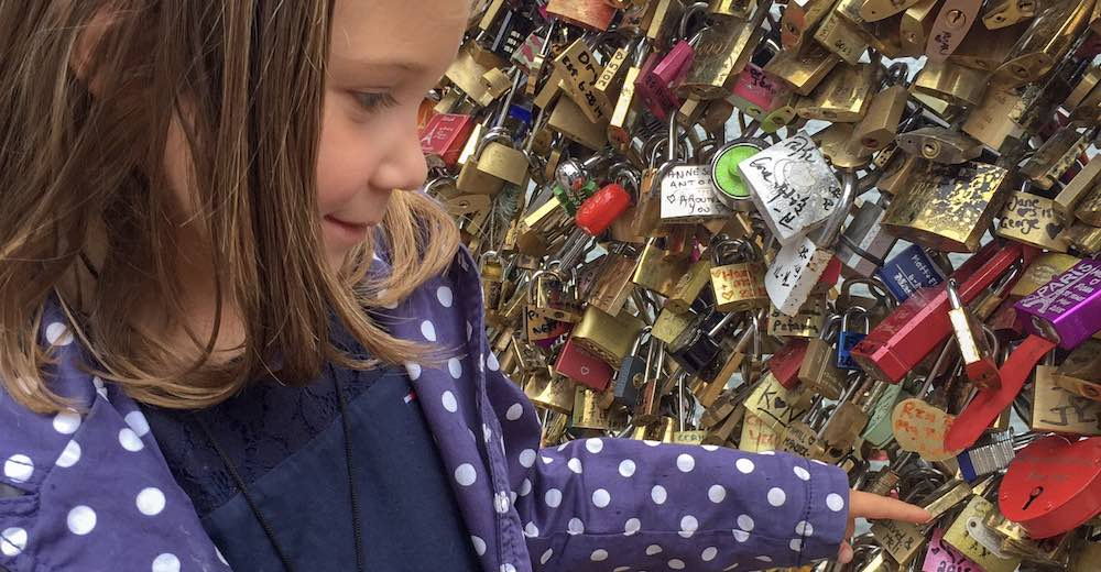 Little girl reading the names on the locks at the Pont des Arts in Paris