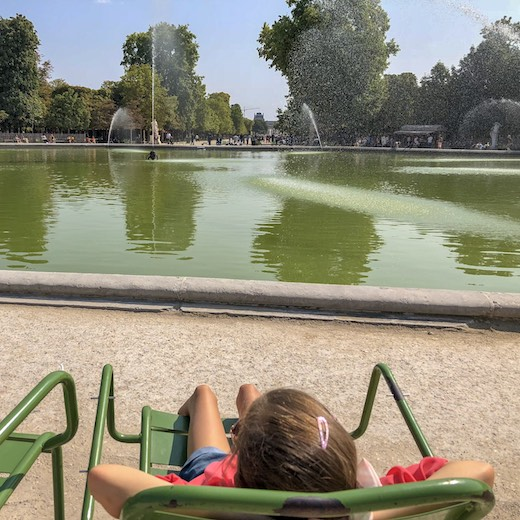 Little girl lounging at Jardin des Tuileries during an exhausting four days in Paris
