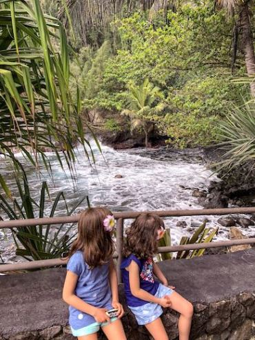 Two little girls sitting on a bench at the Hilo Botanical Gardens and overlooking Onomea Bay