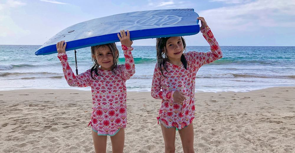 Two CosmopoliGirls using their boogie board to protect themselves from the rain