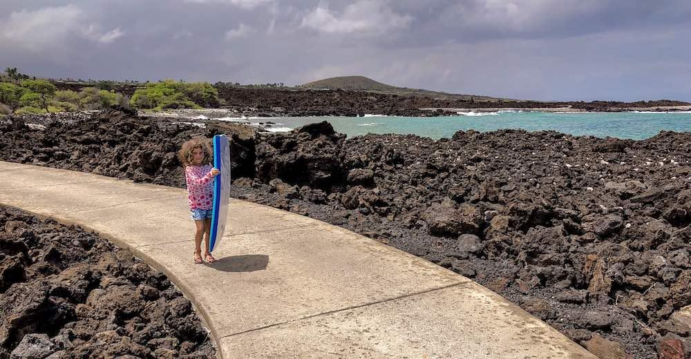 Een klein meisje loopt het pad naar zee af met een boogie-board in de hand