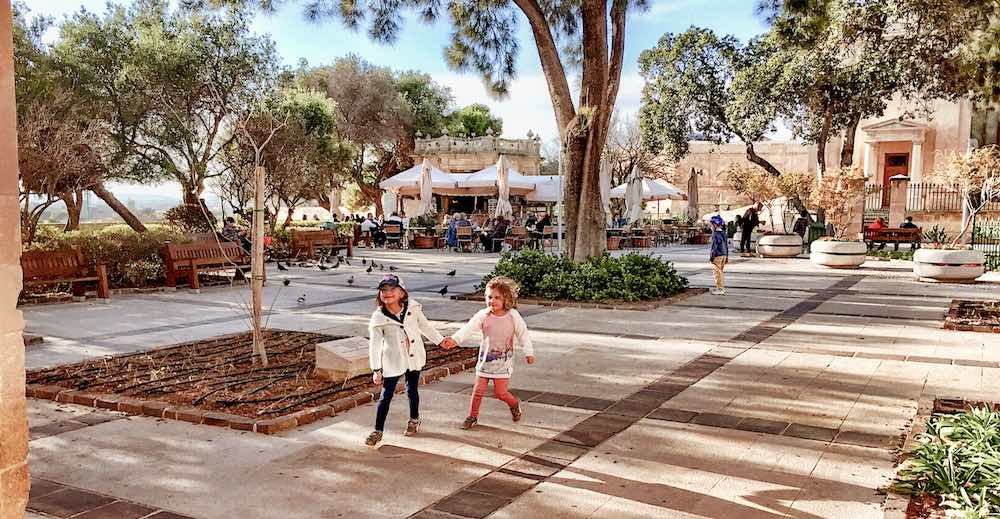 Two little girls exploring the Upper Barrakka Gardens in Valletta, one of the most stunning places to visit in Malta