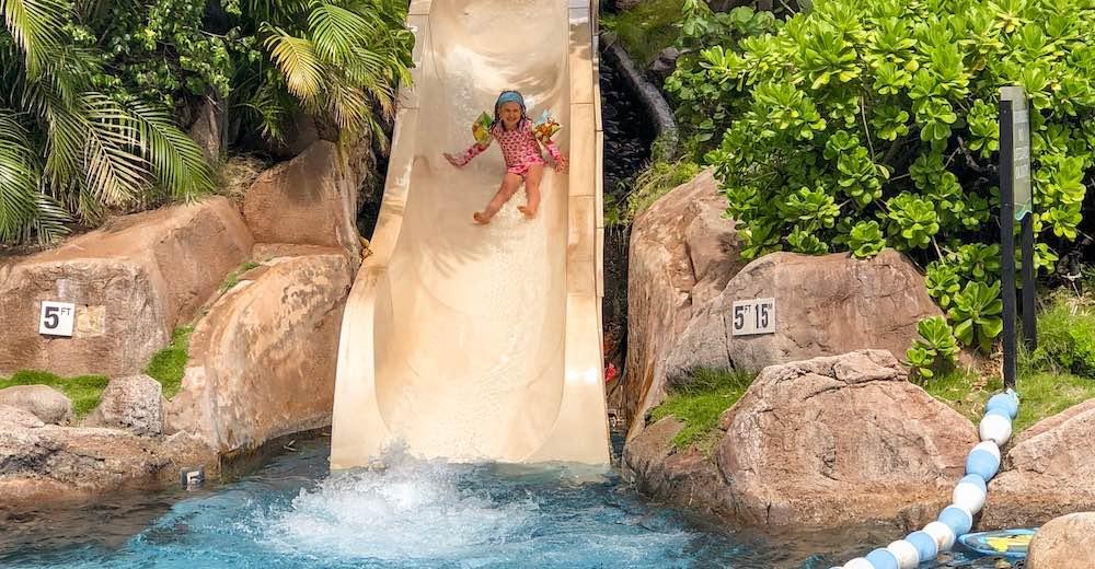 Een meisje glijdt van de glijbaan in het resort op Maui