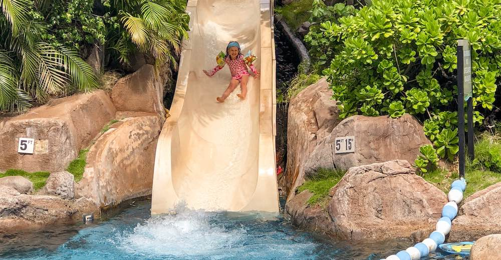 Little girl sliding down the slide at the pool of the Westin Maui Resort and Spa, a great pleace to stay in Maui with kids