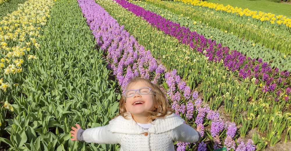 Little girl enjoying the flowers at Keukenhof Holland