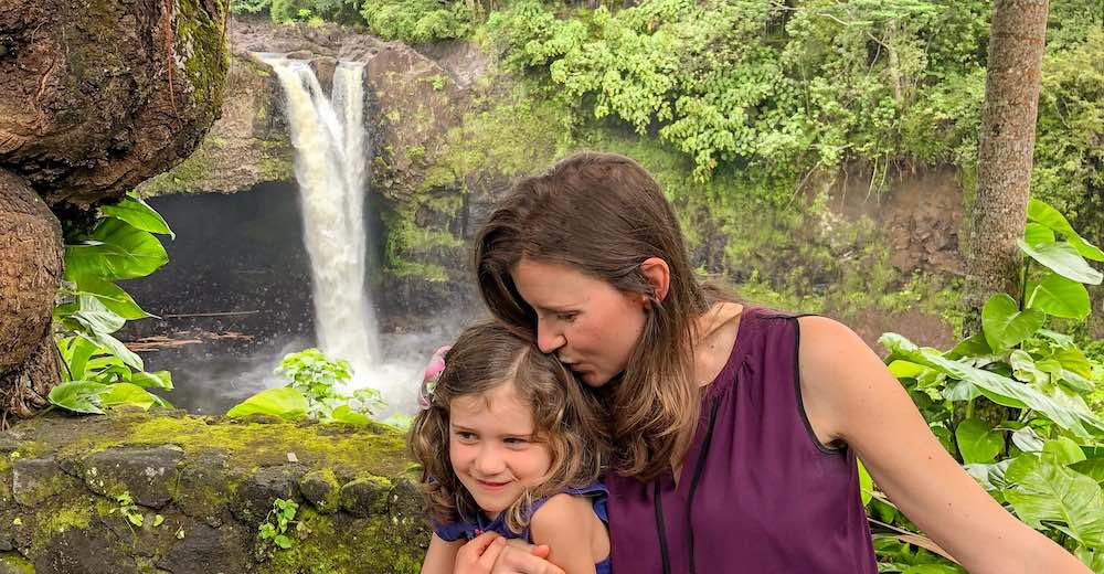 Mother kissing daughter in front of Rainbow falls