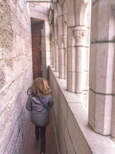 Little girl exploring the gallery at the top of the Belfry of Ghent Belgium