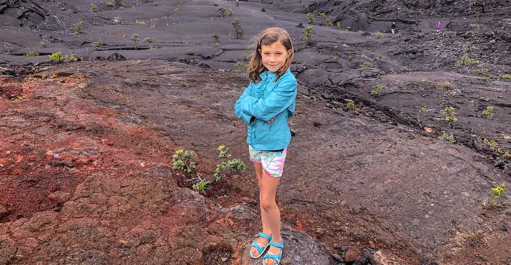 One of the facts about Hawaiian volcanoes is that lava is not always black, as shown by this girl standing on red-colored lava