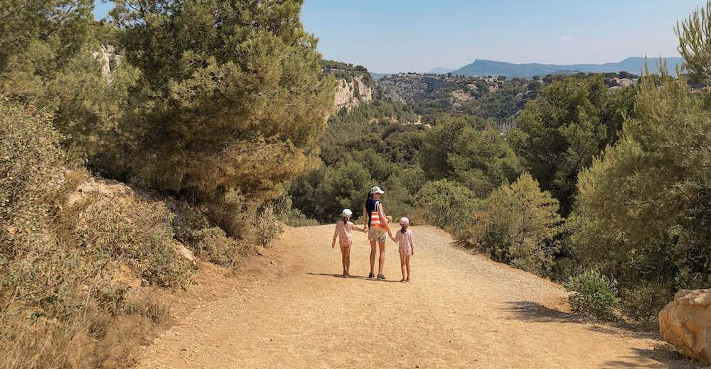 Mother and two girls holding hands on a sandy trail in the Cassis Calanques National Park in the Provence