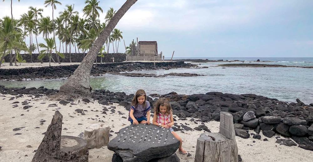 Two little girls playing a game of Hawaiian chess at Pu'uhonua o Honaunau National Historic Park right next to Two Steps beach, one of the best snorkeling beaches on the Big Island