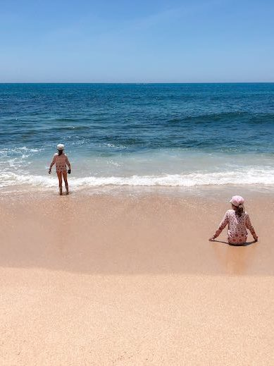 Two little girls playing at the beach in Carvoeiro Portugal