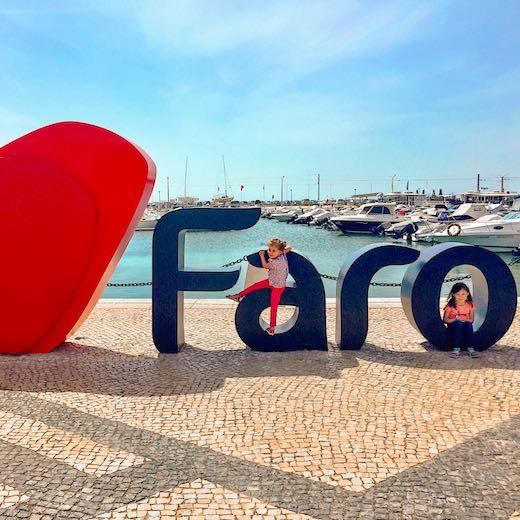 Little girls climbing on the letters of Faro Algarve