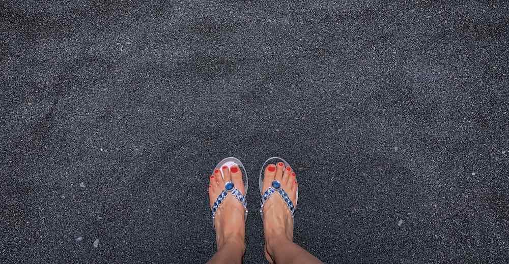 A pair of feet in flip flops on a black sand beach Big Island